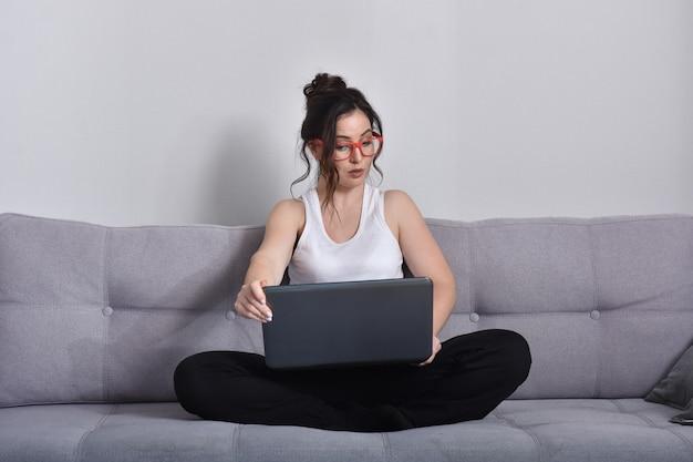 Красивая брюнетка женщина в красных очках на диване, используя ноутбук
