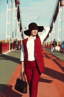晴れた日に橋でポーズをとって赤いパンツスーツと黒い帽子の美しいブルネットの女性