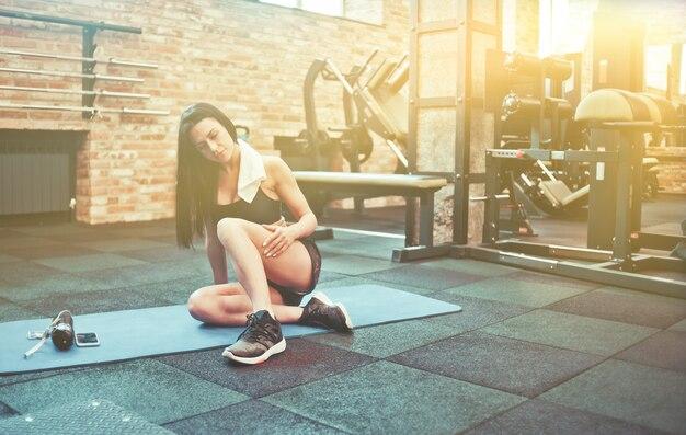 Красивая брюнетка женщина в спортивной одежде с полотенцем на шее, сидя на циновке в тренажерном зале. тренировочный перерыв после тяжелой тренировки