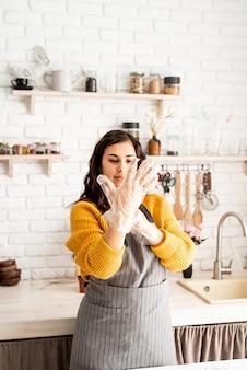 노란색 스웨터와 회색 앞치마에 아름 다운 갈색 머리 여자 장갑을 씌우고 부엌에서 부활절 달걀을 색 준비