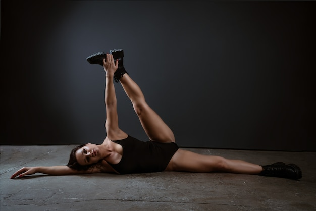 Beautiful brunette woman is engaged in fitness and stretching in a black bodysuit on a dark background