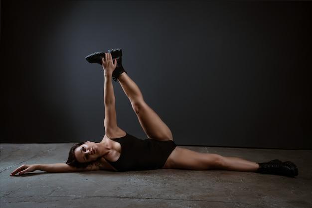 美しいブルネットの女性は、暗い背景に黒いボディースーツでフィットネスとストレッチに従事しています
