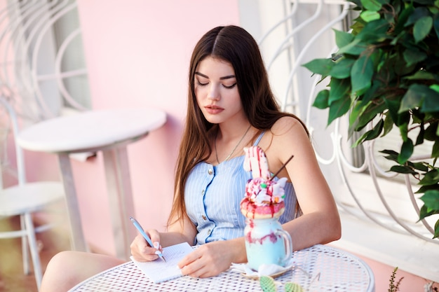Beautiful brunette woman is writing in her dairy while sitting at the table in the outdoor cafe.
