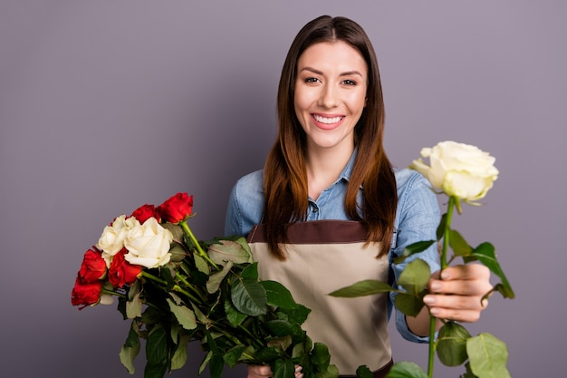 Beautiful brunette woman in jeans shirt posing with bouquet against the purple wall