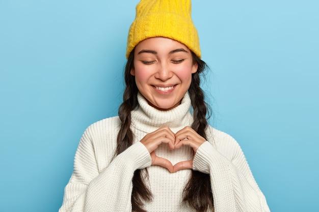 Bella donna castana tiene gli occhi chiusi con piacere, fa un gesto del cuore, esprime il suo vero amore, vestita con un maglione bianco casual