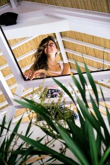 Beautiful brunette woman in loft home in tropical location.