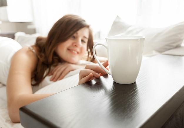 Красивая брюнетка женщина, лежа в постели и принимая чашку кофе