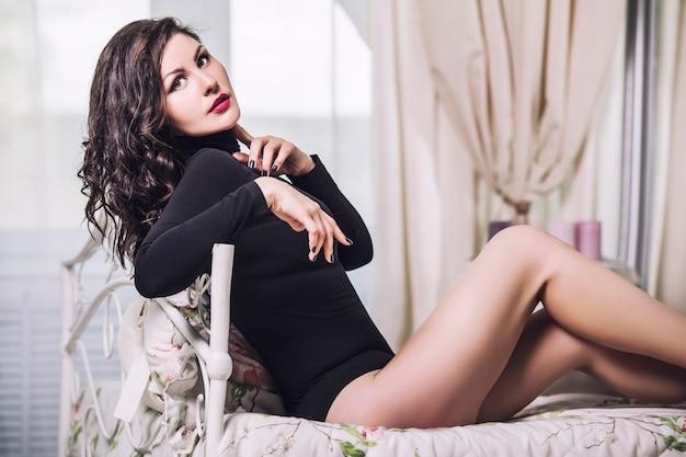 窓に対して寝室の黒いボディースーツのランジェリーで美しいブルネットの女性モデル