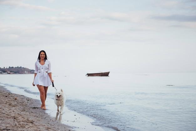 Красивая брюнетка женщина на пляже с собакой гулять