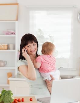 Красивая брюнетка женщина по телефону, держа ее ребенка в ее руках