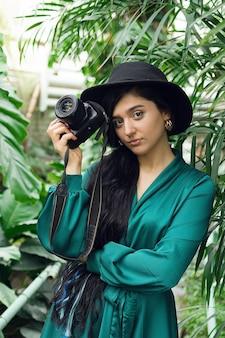 열 대 숲에서 사진 카메라와 함께 아름 다운 갈색 머리 여자 사진 작가. 고품질 사진
