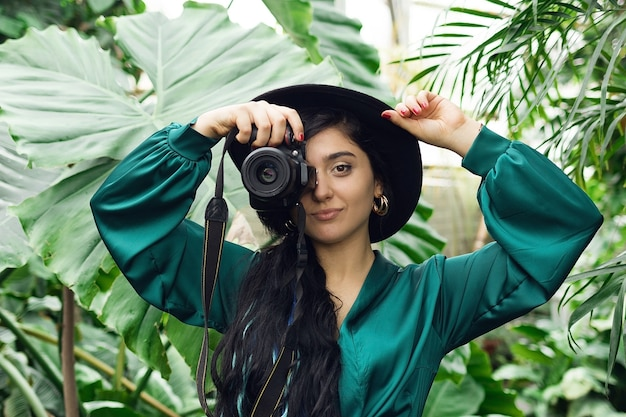 Beautiful brunette woman photographer with photo camera in tropical forest. high quality photo