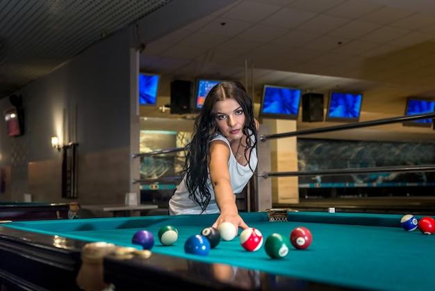 술집에서 당구를 재생하는 아름 다운 갈색 머리 여자