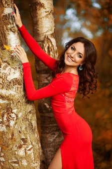 Beautiful brunette woman posing in a luxurious long red dress standing in autumn birch forest.