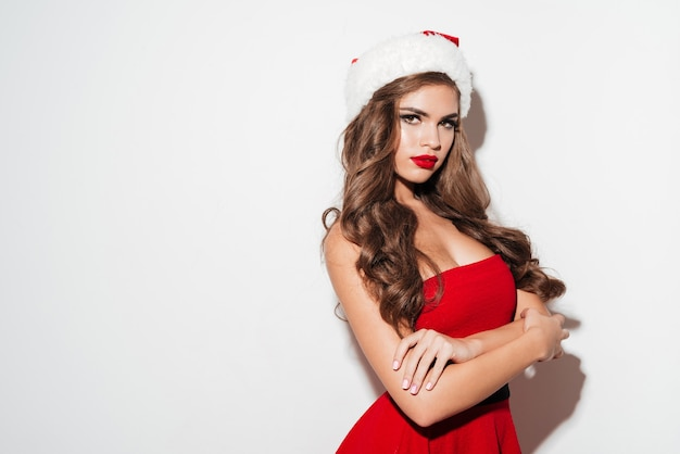 Beautiful brunette woman in red dress and hat with hands crossed isolated over white surface