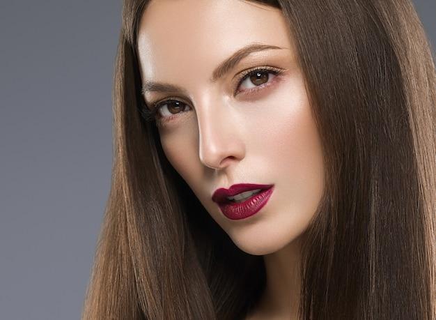 Маникюр губ красивой женщины брюнет красный с крупным планом стороны длинных волос естественный макияж. студийный снимок. цвет фона.