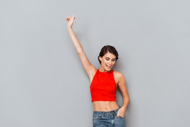 Beautiful brunette woman in red top pointing finger up over gray background