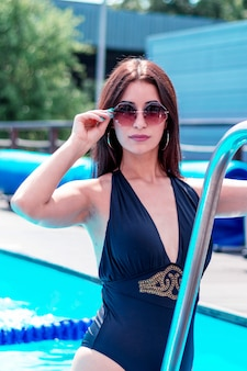 Beautiful brunette woman relaxes in the pool