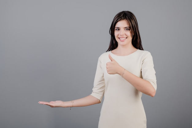 Beautiful brunette woman showing thumbs up with copyspace on hand isolated over grey