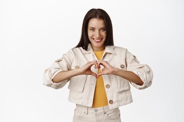 La bella donna castana mostra il cuore, ti amo segno, sorride e sembra carina civettuola, esprime simpatia, come qualcuno, in piedi sul bianco.
