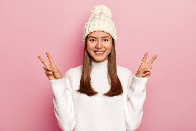 美しいブルネットの女性は勝利または平和のジェスチャーを示し、気持ちよく笑い、元気で、ピンクの壁に隔離されたポンポンとセーターの白い帽子をかぶっています