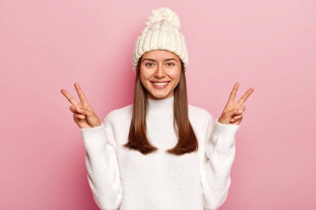 La bella donna castana mostra la vittoria o il gesto di pace, sorride piacevolmente, essendo in alto spirito, indossa il cappello bianco con pompon e maglione, isolato sopra il muro rosa