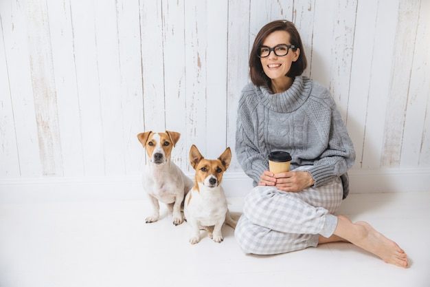 Beautiful brunette woman sits on floor with her two favourite dogs, dressed casually, drinks takeaway coffee. pleased female enjoys calm domestic atmosphere. people and animals, good relations
