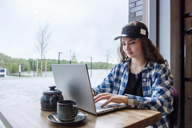 카페에 앉아 노트북 작업을 하거나 기술을 사용하여 인터넷을 통해 학습하는 아름다운 브루네트 여성