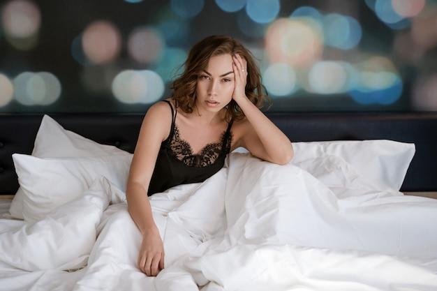 Красивая брюнетка женщина, сидя на кровати, утренняя релаксация