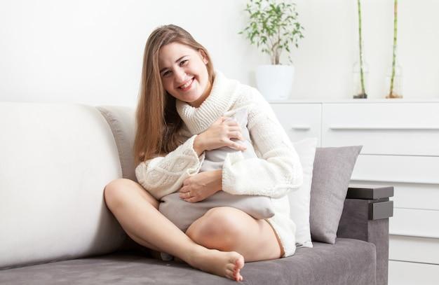 組んだ足と抱き枕でソファに座っている美しいブルネットの女性