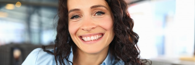 Beautiful brunette woman smiles broadly while sitting in a restaurant. satisfied employee after lunch