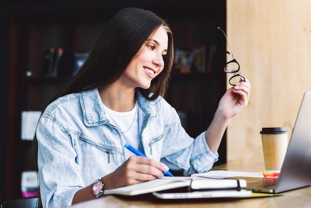 Красивая брюнетка женщина улыбается, держит в руке очки для зрения, использует гаджеты для работы.