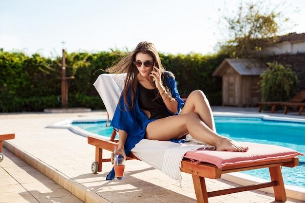 Beautiful brunette woman speaking on phone, sitting near swimming pool