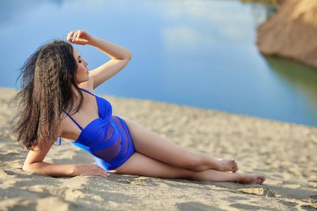 Beautiful brunette woman in swimsuit sandy beach