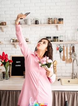 キッチンで携帯電話を使用して自分撮りをしている美しいブルネットの女性