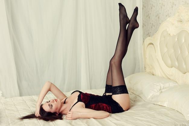 Красивая брюнетка женщина в черном белье в постели
