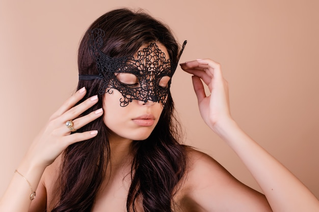 Beautiful brunette woman wearing elegant mask for masquerade isolated over brown