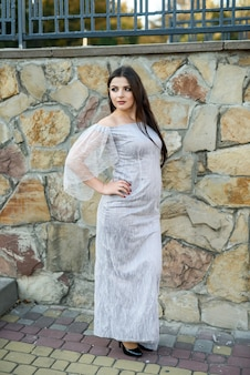 Beautiful brunette woman wearing fashion dress. fashion city photo.