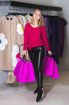 Красивая брюнетка женщина в розовом свитере с хозяйственными сумками в магазине