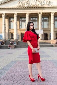 通りでポーズをとって赤いドレスを着て美しいブルネットの女性