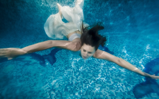 Beautiful brunette woman in white dress swimming underwater at pool