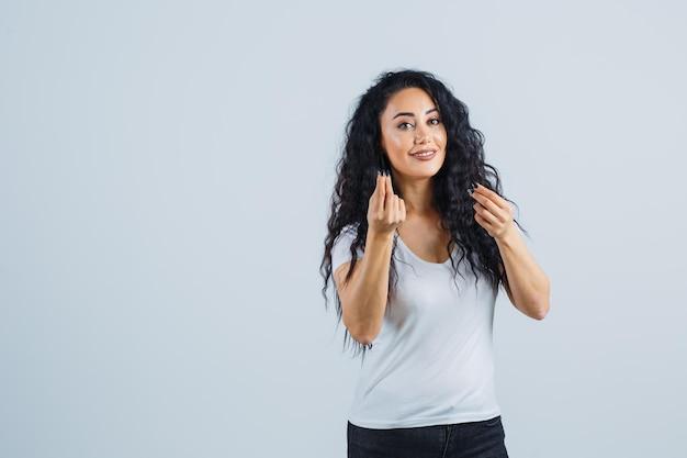 Bella donna castana in una maglietta bianca che fa un gesto
