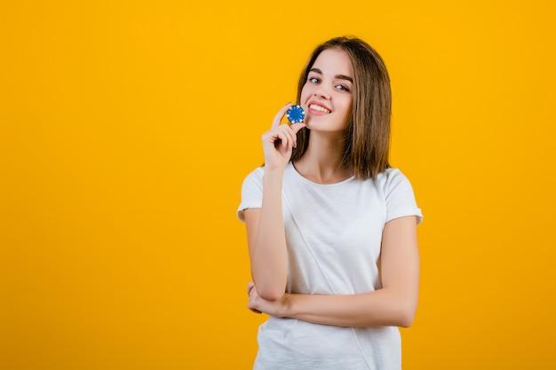 Красивая брюнетка с синим фишкой для покера из онлайн-казино, изолированная на желтом