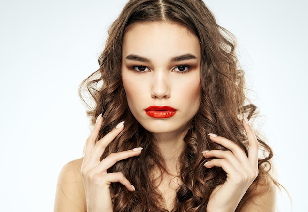 Beautiful brunette woman with bright makeup touches curly hair on her head with her hands