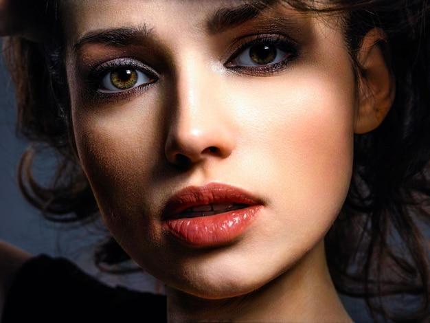 茶色の目を持つ美しいブルネットの女性。スモーキーメイクのファッションモデル。きれいな女性のクローズアップの肖像画は、カメラを見ています。