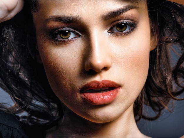 Beautiful brunette woman with  brown eyes. fashion model with a smokey makeup. closeup portrait of a pretty woman looks at camera.