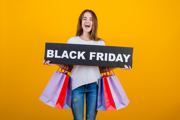 Beautiful brunette woman with colorful shopping bags and copyspace text black friday sign banner isolated over yellow