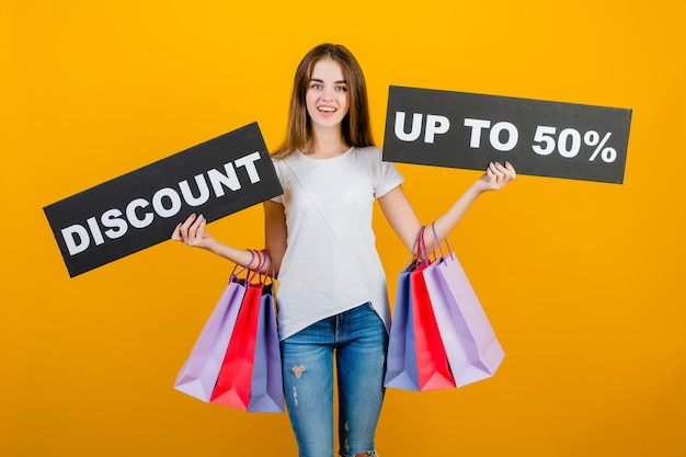 Beautiful brunette woman with colorful shopping bags and copyspace text discount 50% sign banner isolated over yellow