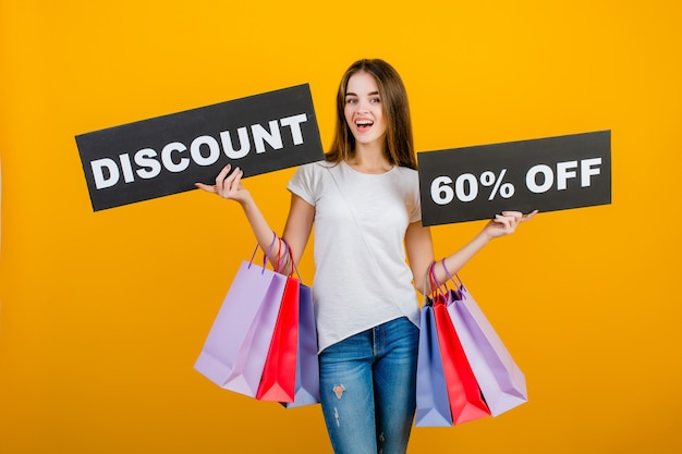 Beautiful brunette woman with colorful shopping bags and copyspace text discount 60% sign banner isolated over yellow