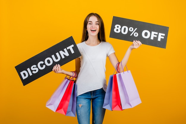 Beautiful brunette woman with colorful shopping bags and copyspace text discount 80% sign banner isolated over yellow